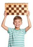 Muchacho con el tablero de ajedrez Foto de archivo libre de regalías