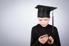 Muchacho con el teléfono móvil en manos Conocimiento, educación y un fondo acertado de la carrera Imagenes de archivo