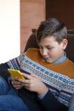 Muchacho con el teléfono móvil que se sienta en un sofá en casa Imagen de archivo