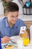 Muchacho con el teléfono que desayuna en cocina Imagenes de archivo