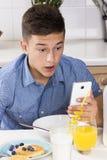 Muchacho con el teléfono que desayuna en cocina Fotografía de archivo libre de regalías