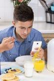 Muchacho con el teléfono que desayuna en cocina Imagen de archivo libre de regalías