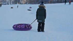 Muchacho con el trineo en una colina de la nieve almacen de metraje de vídeo