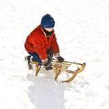 Muchacho con el trineo largo en paisaje nevado Foto de archivo