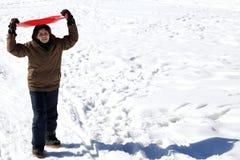 Muchacho con el trineo rojo de la nieve en invierno Imágenes de archivo libres de regalías