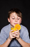 Muchacho con el zumo de naranja Foto de archivo