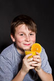 Muchacho con el zumo de naranja Imagen de archivo