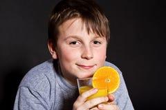 Muchacho con el zumo de naranja Foto de archivo libre de regalías
