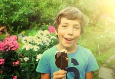Muchacho con helado esquimal en el jardín del verano Imágenes de archivo libres de regalías
