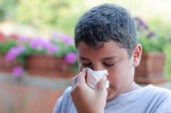 Muchacho con la alergia que sopla su nariz Foto de archivo libre de regalías