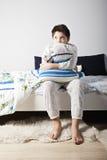 Muchacho con la almohada que mira de lado Imagenes de archivo