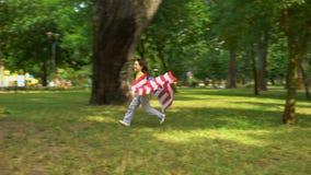 Muchacho con la bandera americana que corre en el parque, celebración del Día de la Independencia, futuro almacen de video