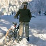 Muchacho con la bici del invierno Fotos de archivo