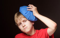 Muchacho con la bolsa de hielo en su cabeza Imagenes de archivo