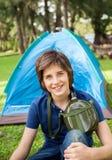 Muchacho con la botella de agua en el sitio para acampar Imagen de archivo