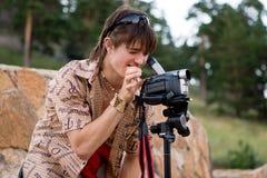 Muchacho con la cámara de vídeo en el trípode Fotos de archivo libres de regalías