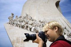 Muchacho con la cámara en el monumento en Portugal. Foto de archivo libre de regalías