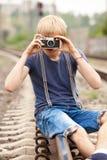 muchacho con la cámara en los ferrocarriles Fotos de archivo
