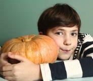 Muchacho con la calabaza entera cruda para Halloween Fotografía de archivo
