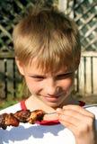 Muchacho con la carne asada a la parilla Foto de archivo libre de regalías