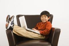 Muchacho con la computadora portátil Fotos de archivo