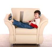 Muchacho con la computadora portátil y el auricular. imágenes de archivo libres de regalías