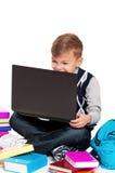 Muchacho con la computadora portátil y los libros Foto de archivo