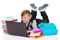 Muchacho con la computadora portátil y los libros Foto de archivo libre de regalías