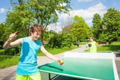 Muchacho con la estafa lista para jugar en tenis de mesa Imagen de archivo libre de regalías