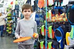 Muchacho con la estafa y bola para el tenis de la playa en tienda Imágenes de archivo libres de regalías