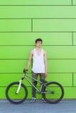 Muchacho con la estancia de plata de la bici en el fondo verde de la pared Fotografía de archivo