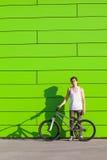 Muchacho con la estancia de plata de la bici en el fondo verde de la pared Fotos de archivo libres de regalías