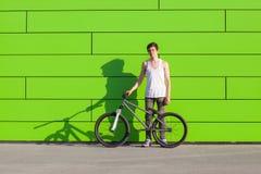 Muchacho con la estancia de plata de la bici en el fondo verde de la pared Imagen de archivo libre de regalías