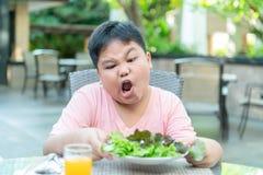 Muchacho con la expresi?n del repugnancia contra verduras fotografía de archivo libre de regalías