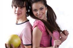 Muchacho con la fruta y la muchacha en alineada rosada Foto de archivo