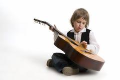 Muchacho con la guitarra en un blanco   Foto de archivo