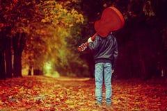 Muchacho con la guitarra que camina en el camino del otoño Visión posterior Foto de archivo libre de regalías