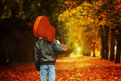 Muchacho con la guitarra que camina en el camino del otoño Visión posterior Fotografía de archivo libre de regalías