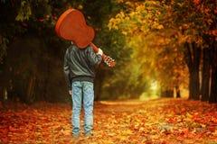 Muchacho con la guitarra que camina en el camino del otoño Visión posterior Imágenes de archivo libres de regalías