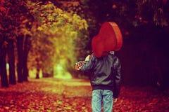 Muchacho con la guitarra que camina en el camino del otoño Visión posterior Ima entonado Fotos de archivo