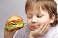 Muchacho con la hamburguesa Fotos de archivo