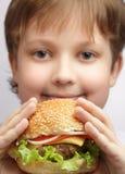 muchacho con la hamburguesa grande Foto de archivo