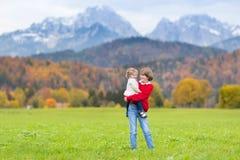Muchacho con la hermana del niño en campo en mountainsa Foto de archivo libre de regalías