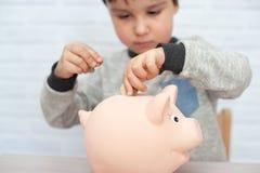 Muchacho con la hucha del cerdo niñez, dinero, inversión y concepto feliz de la gente imagen de archivo