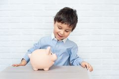 Muchacho con la hucha del cerdo niñez, dinero, inversión y concepto feliz de la gente foto de archivo