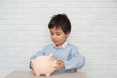 Muchacho con la hucha del cerdo niñez, dinero, inversión y concepto feliz de la gente imagen de archivo libre de regalías