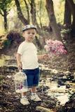 Muchacho con la lila y la jaula de pájaros en una charca Imagen de archivo