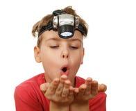 Muchacho con la linterna en su cabeza en blanco Fotografía de archivo libre de regalías
