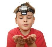 Muchacho con la linterna en su cabeza en blanco Fotos de archivo libres de regalías