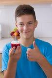 Muchacho con la magdalena en cocina Imagen de archivo libre de regalías